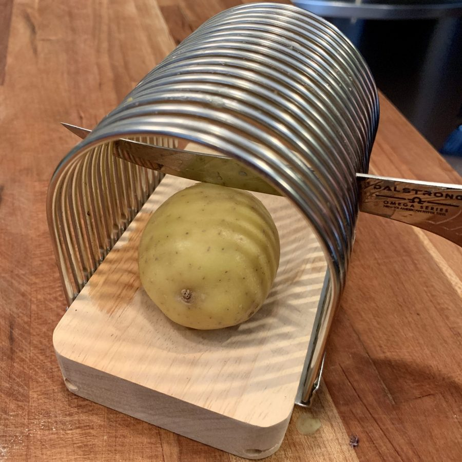 Cutting slits in potato to make hasselback potatoes