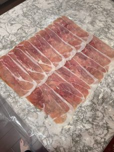 Overlapped Pieces of Prosciutto on Plastic Wrap