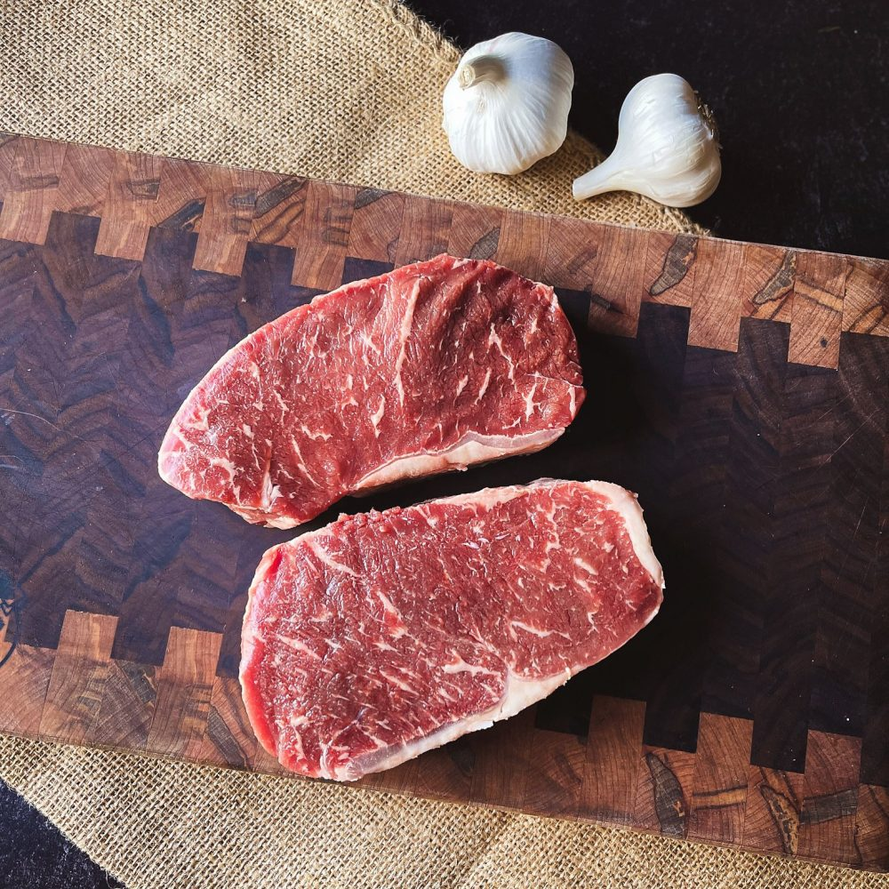 a picture of two new york strip steaks